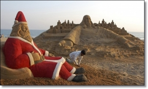 Sand artist Sudarsan Patnaik creates sand sculptures of Santa Claus and Jesus Christ on Christmas eve at a beach in Puri